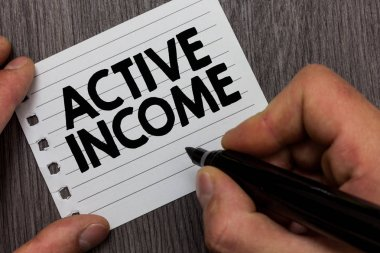Conceptual hand writing showing Active Income. Business photo showcasing Royalties Salaries Pensions Financial Investments Tips Man holding marker notebook page Wooden background.
