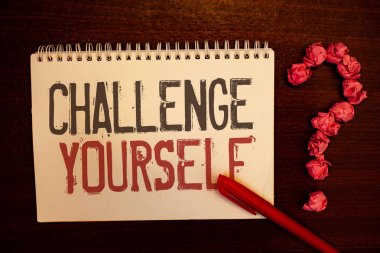 Handwriting text Challenge Yourself. Concept meaning Overcome Confidence Strong Encouragement Improvement Dare Reddish paper balls structures question mark red pen notebook browny desk.