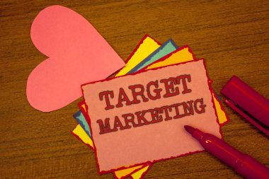 Handwriting text writing Target Marketing. Concept meaning Market Segmentation Audience Targeting Customer Selection Text colorful paper notes pink heart red marker open cap desk message stock vector