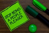 Text sign showing Stop Being A People Pleaser. Conceptual photo Do what you like not things other people want Written on sticky note two markers laid on wooden floor green ball.