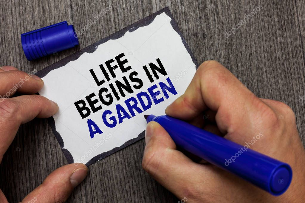 Handwriting text Life Begins In A Garden. Concept meaning Agriculture Plants growing loving for gardening Gray wooden deck hand hold black marker written black lined sticky note.