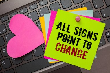 Text sign showing All Signs Point To Change. Conceptual photo Necessity of doing things differently new vision Bright colorful written papers pinch by pin pink heart on computer keyboard.
