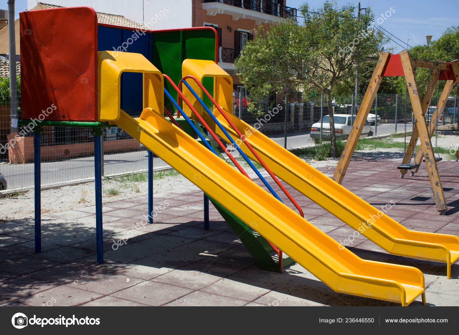 Screened Playground With Two Colorful Slides And Swing