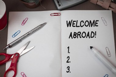 Text sign showing Welcome Abroad. Conceptual photo something that you say when someone gets on ship Scissors and writing equipments plus math book above textured backdrop.