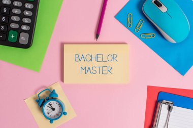 Conceptual hand writing showing Bachelor Master. Business photo text An advanced degree completed after bachelor s is degree Mouse calculator sheets marker clipboard clock color background.