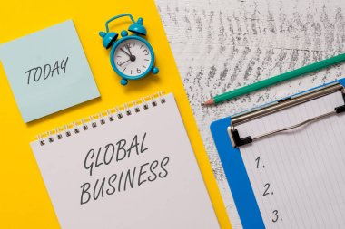 Conceptual hand writing showing Global Business. Business photo showcasing Trade and business system a company doing across the world Spiral notepad sheet marker alarm clock wooden background.