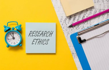 Word writing text Research Ethics. Business concept for interested in the analysis ofethicalissues that raised Notepads clipboard colored paper sheet marker alarm clock wooden background.