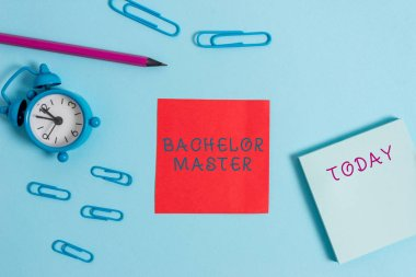 Writing note showing Bachelor Master. Business photo showcasing An advanced degree completed after bachelor s is degree Alarm clock wakeup clips notepad sticky note pencil colored background.