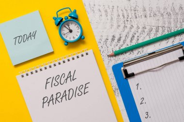 Conceptual hand writing showing Fiscal Paradise. Business photo showcasing The waste of public money is a great concern topic Spiral notepad sheet marker alarm clock wooden background.