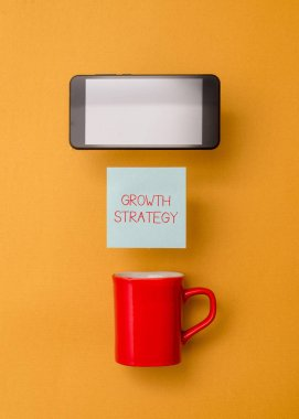 Word writing text Growth Strategy. Business concept for Strategy aimed at winning larger market share in shortterm Coffee cup colored sticky note electronic device yolk color background.
