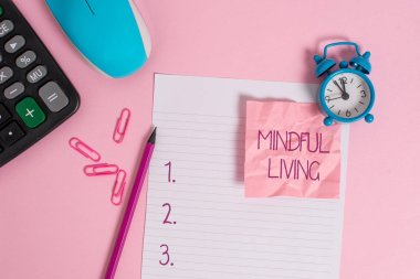 Conceptual hand writing showing Mindful Living. Business photo showcasing Fully aware and engaged on something Conscious and Sensible Calculator clock mouse crushed note pencil color background.