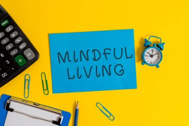 Handwriting text Mindful Living. Concept meaning Fully aware and engaged on something Conscious and Sensible Clipboard sheet clips note calculator pencil alarm clock colored background.