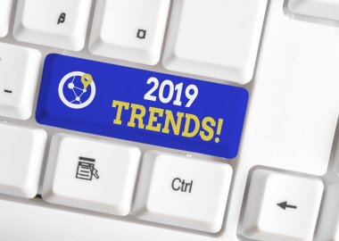 Conceptual hand writing showing 2019 Trends. Business photo showcasing general direction in which something is developing or changing White pc keyboard with note paper above the white background.
