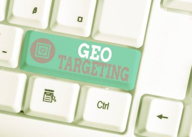 Writing note showing Geo Targeting. Business photo showcasing Digital Ads Views IP Address Adwords Campaigns Location White pc keyboard with note paper above the white background.