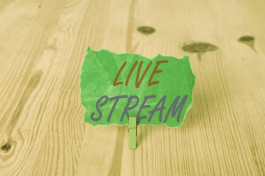 Text sign showing Live Stream. Conceptual photo transmit or receive video and audio coverage over Internet Empty reminder wooden floor background green clothespin groove slot office.