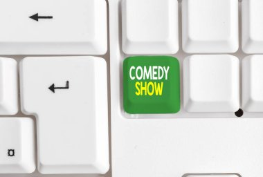 Conceptual hand writing showing Comedy Show. Business photo text Funny program Humorous Amusing medium of Entertainment White pc keyboard with note paper above the white background.