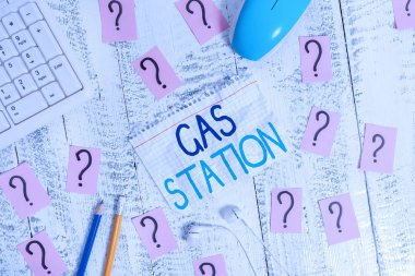 Writing note showing Gas Station. Business photo showcasing for servicing motor vehicles especially with gasoline and oil Writing tools and scribbled paper on top of the wooden table.