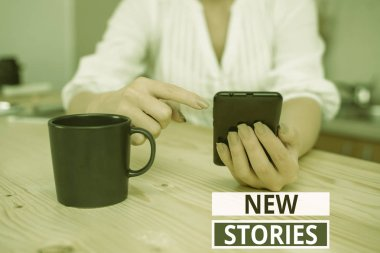 Text sign showing New Stories. Conceptual photo imaginary or real showing and events told for entertainment woman using smartphone office supplies technological devices inside home.