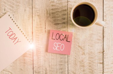 Conceptual hand writing showing Local Seo. Business photo text This is an effective way of marketing your business online Stationary placed next to a coffee cup above wooden table.