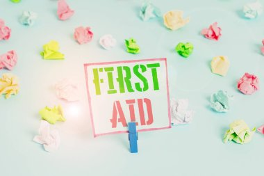 Word writing text First Aid. Business concept for Practise of healing small cuts that no need for medical training Colored crumpled papers empty reminder blue floor background clothespin.