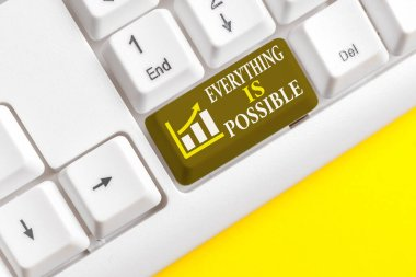 Conceptual hand writing showing Everything Is Possible. Business photo text Any outcome could occur Anything can happen White pc keyboard with note paper above the white background.