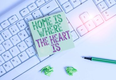 Writing note showing Home Is Where The Heart Is. Business photo showcasing Your house is where you feel comfortable and happy Green note paper with pencil on white background and pc keyboard.
