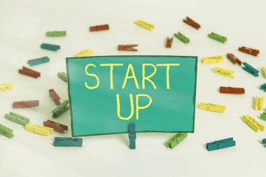 Word writing text Start Up. Business concept for in the early process of establishing and developing a new business Colored clothespin papers empty reminder white floor background office.