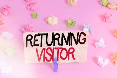 Writing note showing Returning Visitor. Business photo showcasing who had visited before and come back to your site Colored crumpled papers empty reminder pink floor background clothespin.