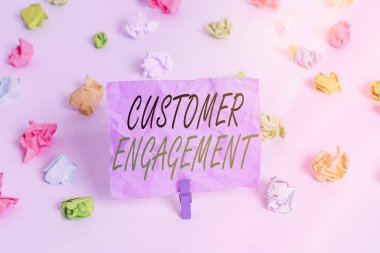 Word writing text Customer Engagement. Business concept for communication connection between a consumer and a brand Colored crumpled papers empty reminder white floor background clothespin.