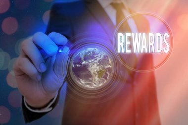 Writing note showing Rewards. Business photo showcasing certain number or percentage you earn for every dollar you charge Elements of this image furnished by NASA.