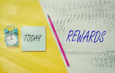 Writing note showing Rewards. Business photo showcasing certain number or percentage you earn for every dollar you charge Notepad marker colored paper sheets retro alarm clock wooden background.