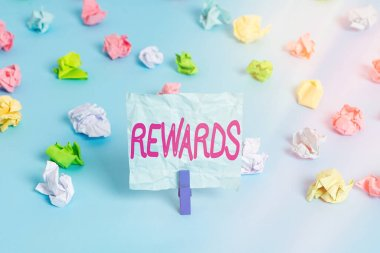 Handwriting text Rewards. Concept meaning certain number or percentage you earn for every dollar you charge Colored crumpled papers empty reminder blue floor background clothespin.