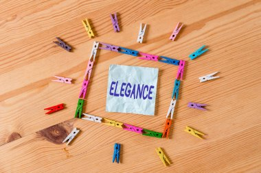 Handwriting text Elegance. Concept meaning scientific precision, neatness, and simplicity of something Colored clothespin papers empty reminder wooden floor background office.
