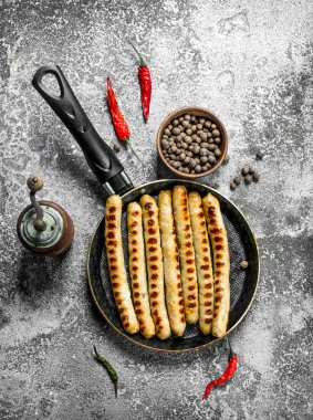 Fried sausages with spices in a frying pan. On rustic background.