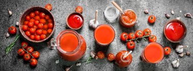 Tomato juice, pickled tomatoes and sauce. On rustic background.
