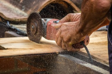 A Carpenter Man Cutting a Piece of Wood for Roofing Work