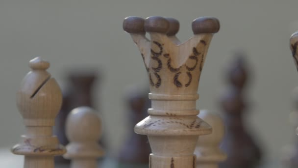 Wooden chess game on a table in a camera slide from left to right. Against sun with lens flare
