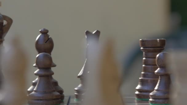 Wooden chess game on a table in a camera slide from right to left.