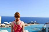 Fotografie Schöne schlanke, dünne Mädchen in ein rosa T-shirt mit einem Zopf auf dem Hintergrund eines Pools mit Sonnenschirmen und Sonnenliegen und ein blaues Meer in einem warmen tropischen Resort in Ägypten