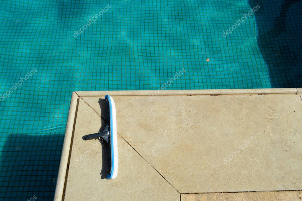 A blue brush with a sponge for cleaning the cleaning of the pool tending the tiles on the background of the pool with shallow square ceramic tiles and clear water
