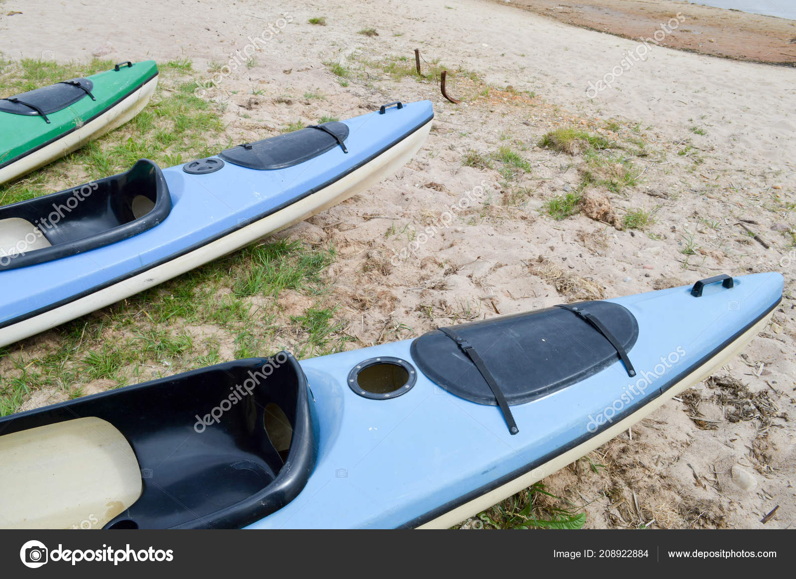 A lot of blue and green canoe kayaks with front parts of the