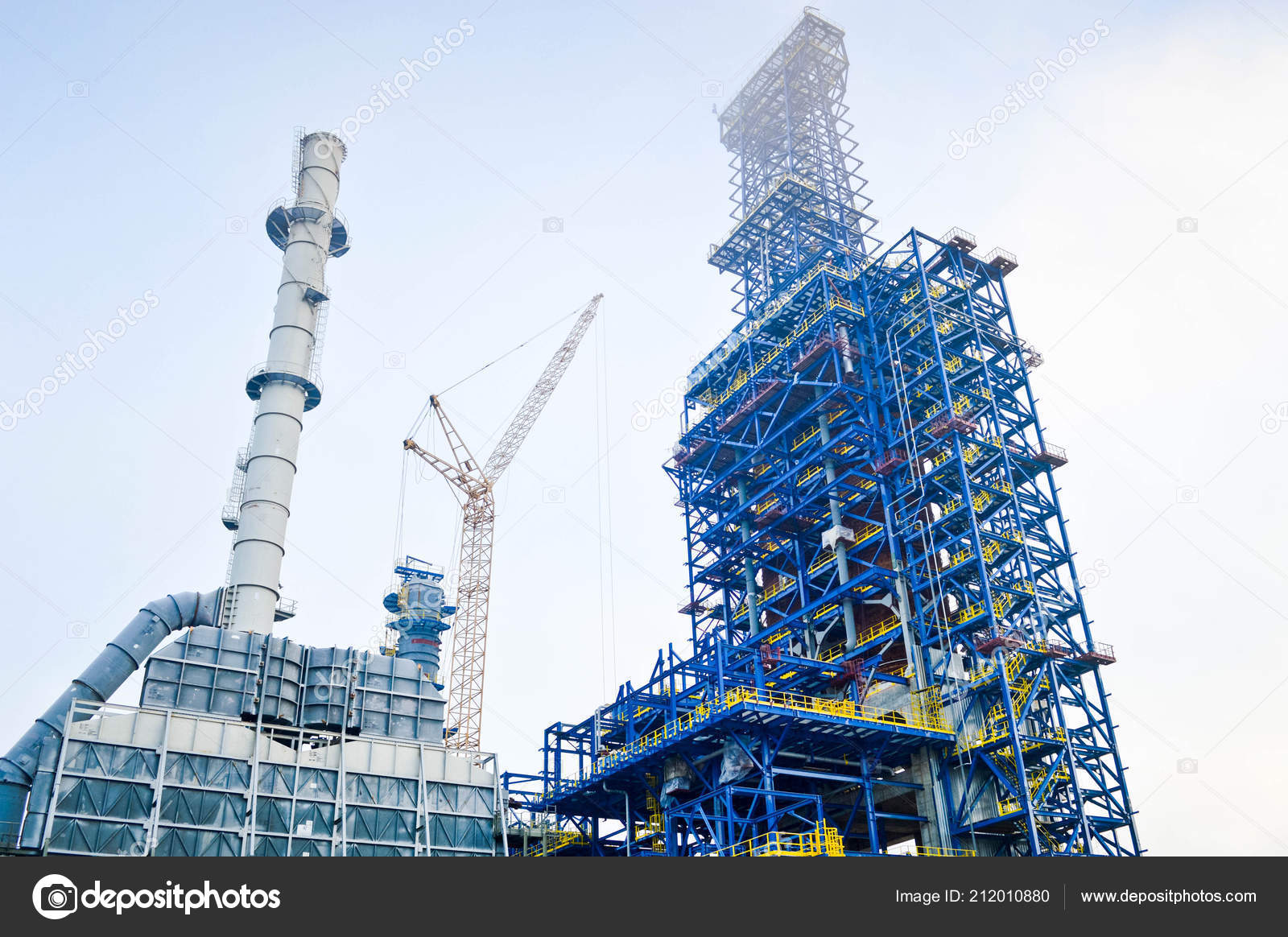 Construction with cranes of a large blue chemical plant at an oil