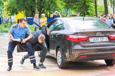A policeman, a road policeman in a blue uniform, fights, delays, arrests a criminal driver of a car. Belarus, Minsk, 08.08.2018