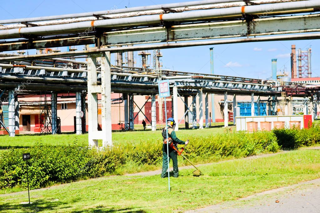 The worker in a protective suit and mask uses a special device to mow the grass on a sunny summer day. Lawn mower in the hands of a man. Against the backdrop of pipes on chemical production