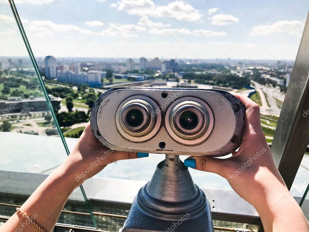 Viewing stationary binoculars against a white-blue sky. Gray binoculars on the viewing platform at height in the hands of a girl with multi-colored nails. From the roof overlooking the beautiful city