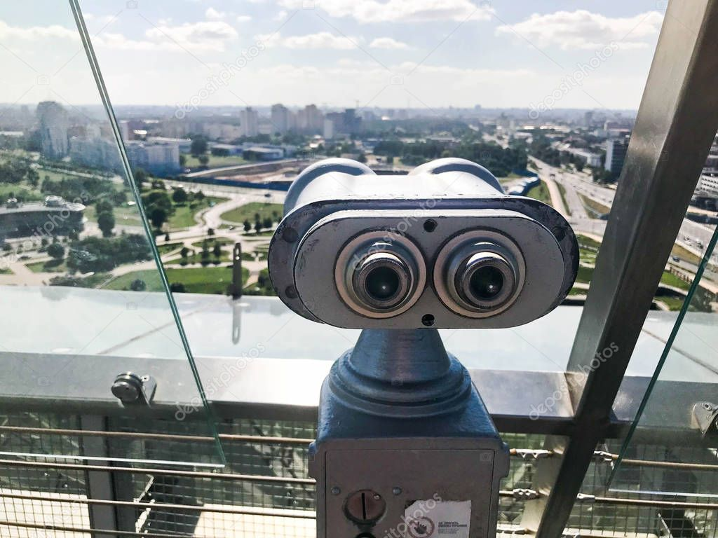 Viewing coin stationary binoculars against a white-blue sky in profile. Gray metal binoculars on the viewing platform at a height. From the roof overlooking the beautiful green city