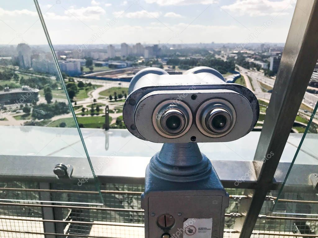 Monetary stationary binoculars on the background of sky. Gray metal binoculars on the viewing platform at height installed at the edge of the roof. From the roof you can see the beautiful green city