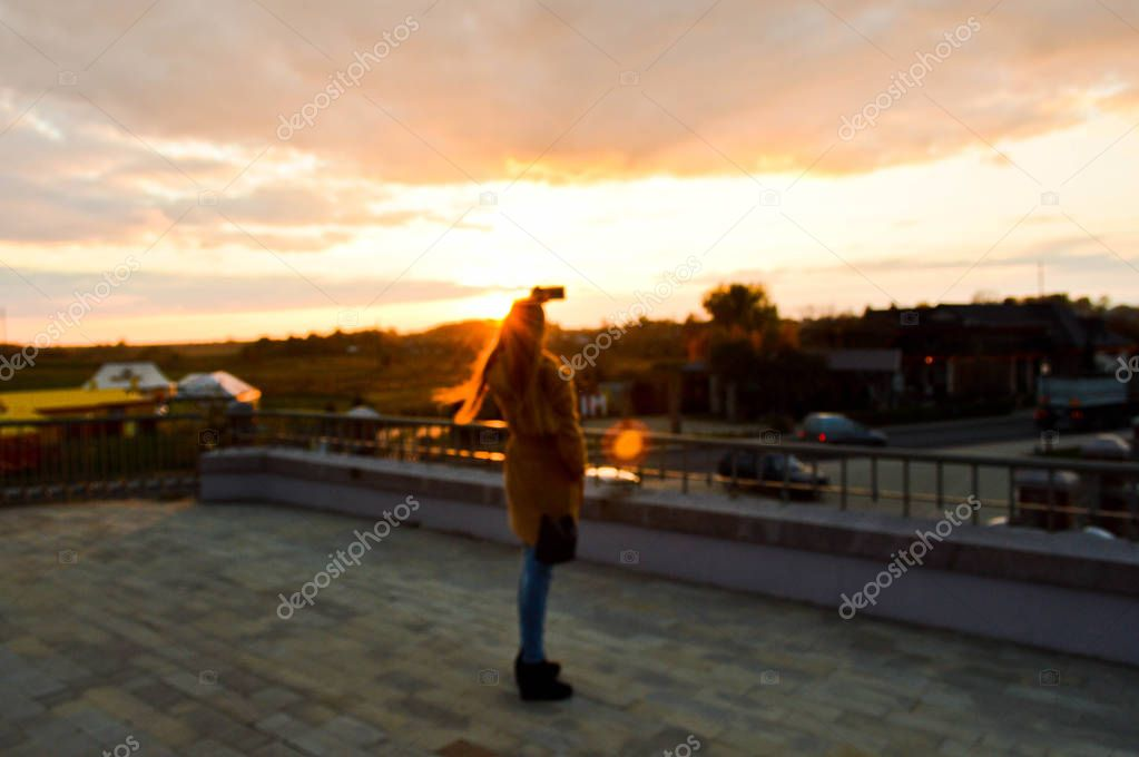 Beautiful girl, a woman in a brown coat photographs the sunset on the phone, a smartphone for social networks