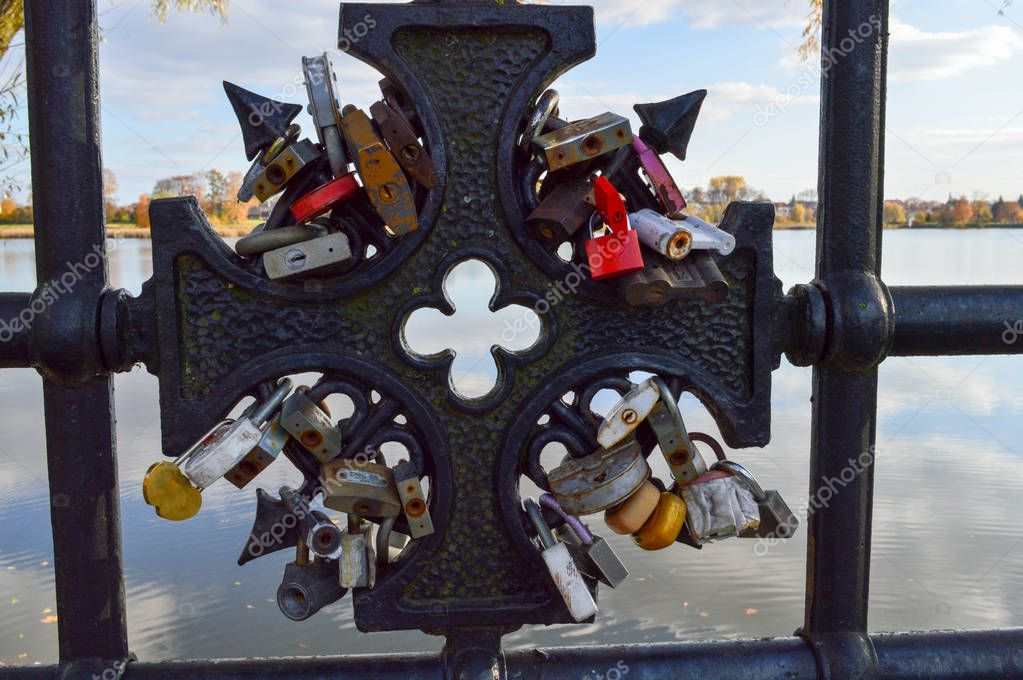A lot of barn locks hang hitched to the bridge railing. Wedding tradition to hang locks on bridges for eternal love