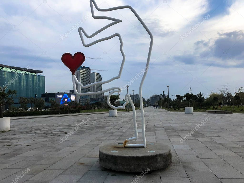 Abstract statues, small architectural forms with a man holding a heart on a skateboard on Batumi Primorsky Boulevard or Batumi Beach. Georgia, Batumi, April 17, 2019